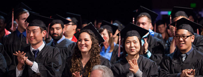 A group of graduates at commencement applaud