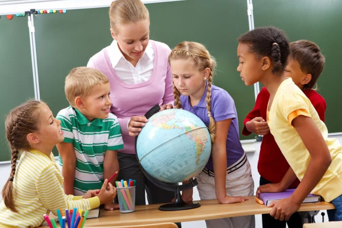 Teacher showing group of students a globe