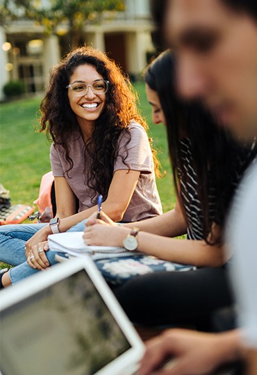 A student smiles while studying with a group on a lawn.