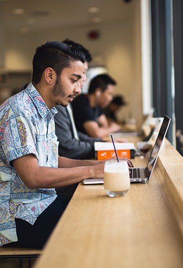 A student types on a laptop at a coffee shop.
