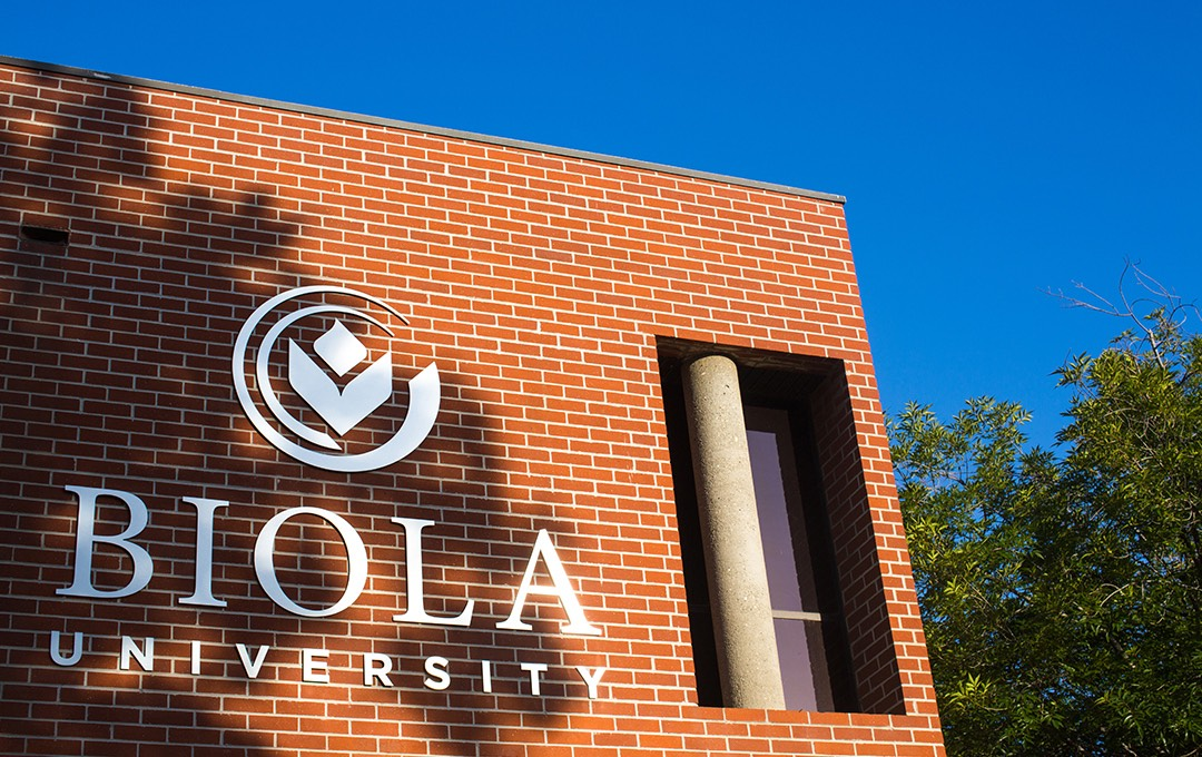 The sun shines on the Biola logo by the Admissions Welcome Center.