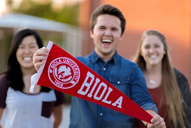 A group of students smile while one holds up a Biola University banner.