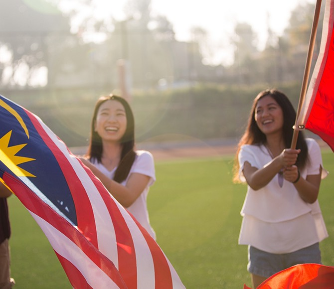 Students wave flags from their home countries.