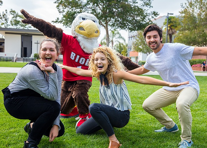 A group of students smiles with the Biola Eagle mascot.