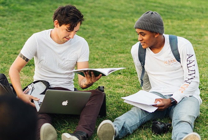 Two students discuss notes while sitting on a grass lawn.