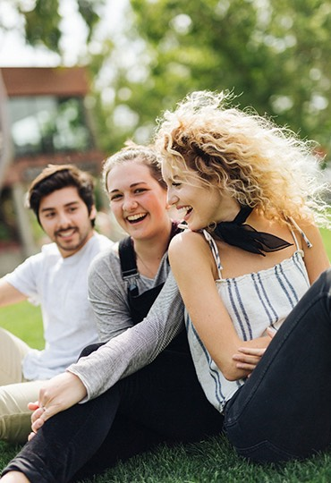 A group of students laugh together on Metzger Lawn.