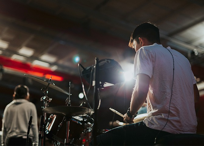 Reverse shot of a drummer, performing on a stage.