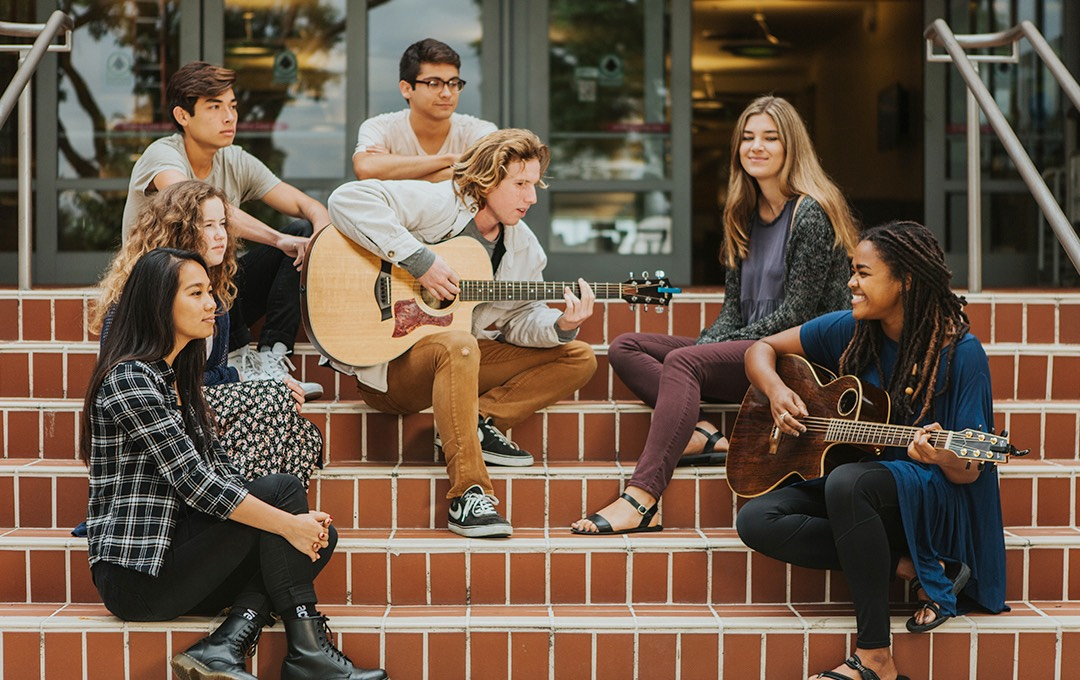 A diverse group of students plays guitar and sings on the steps of the library.