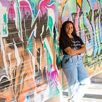 A female student stands in front of a graffiti art installation at SCORR conference.