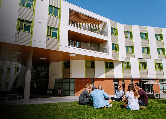 A group of students hang out on the lawn in front of Blackstone Hall.