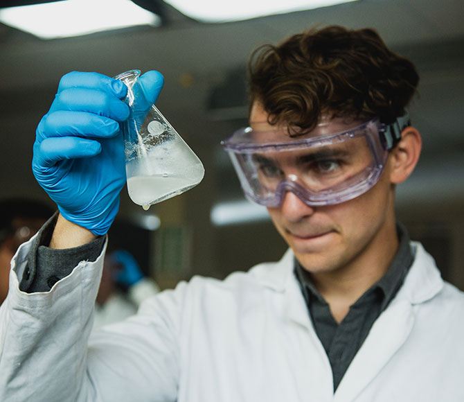 A student wearing goggles and latex gloves examines a beaker filled with liquid.