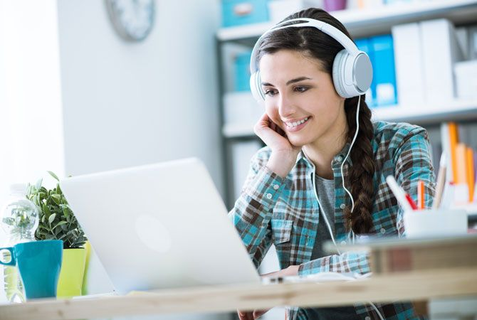 A girl wearing headphones works on a laptop