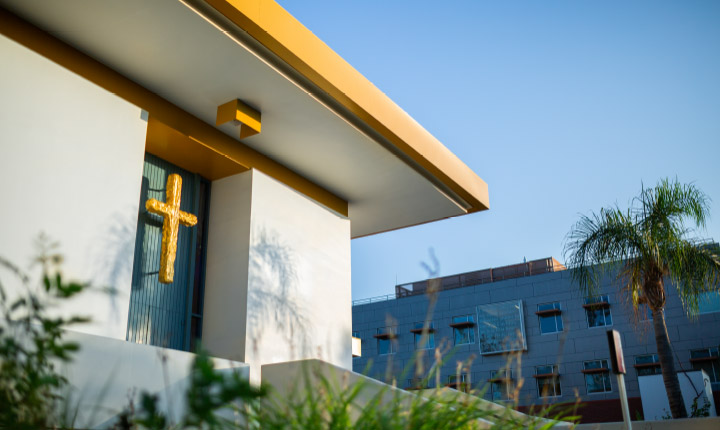 Exterior of Calvary Chapel, featuring large gold cross on blue double doors