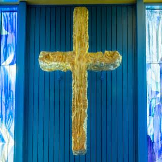 Golden cross sculpture mounted above blue doors