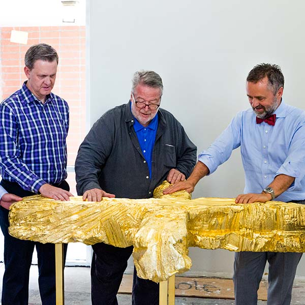 Dr. Barry Corey and others touch the golden cross sculpture before it is mounted