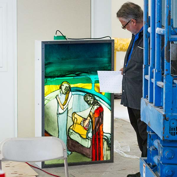 Peter Brandes examines a panel of stained glass