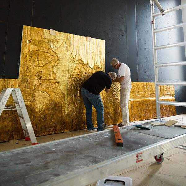 Two men install the gold relief sculpture behind the stage