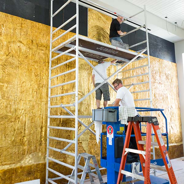 Installation of the gold relief continues with scaffolding and a ladder