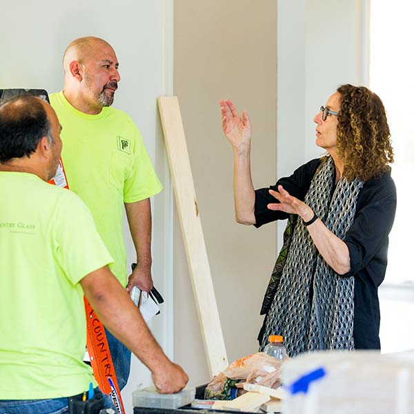 Maja Lisa Engelhardt speaks to two men from the stained glass installation crew