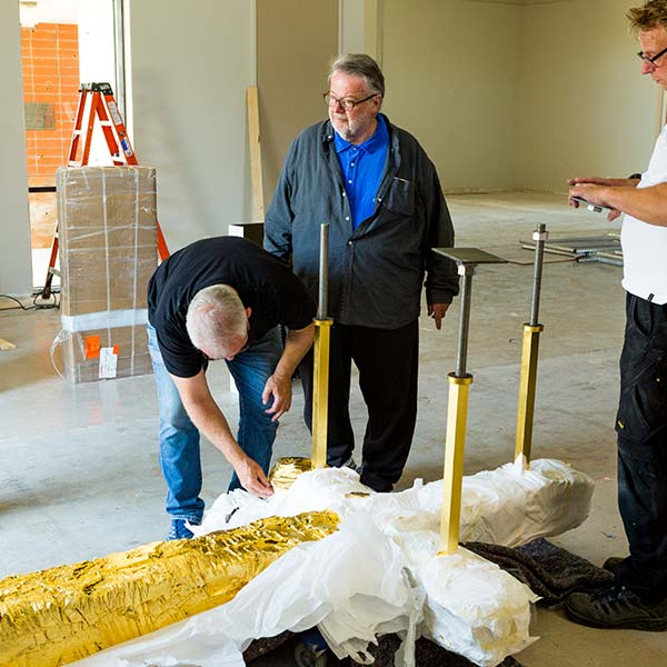 Peter Brandes and others unwrap the cross sculpture