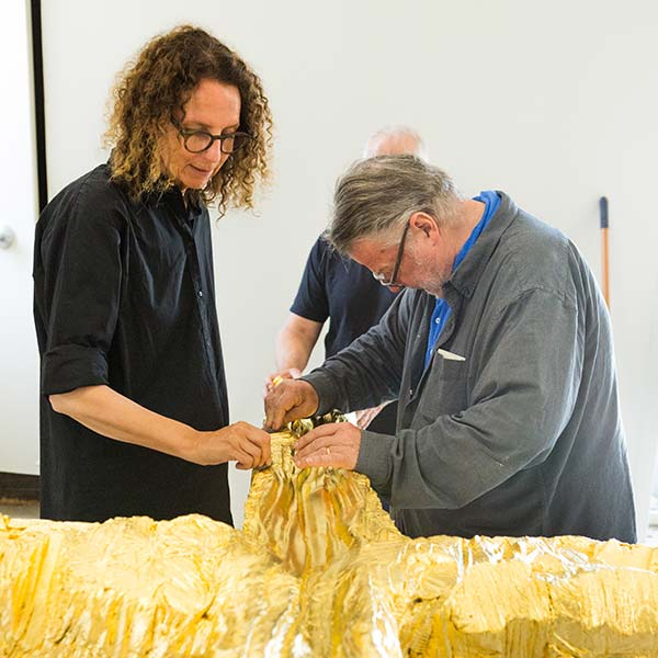Maja Lisa Engelhardt and Peter Brandes examine the cross sculpture before it is mounted