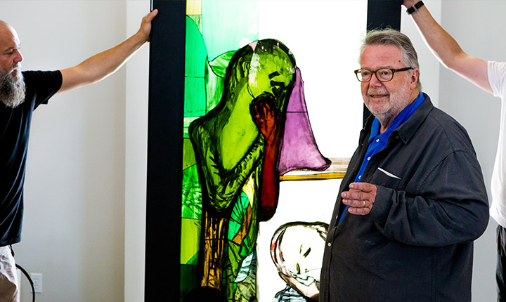 One of the artists with a one of the stained glass pieces