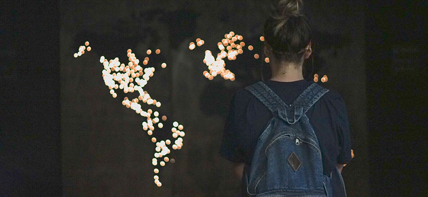 A girl looks at lights in the shape of the nations
