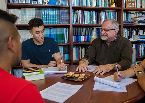 A male faculty member meets with three students around a table in his office