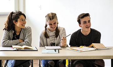 Three students sit together at a table during class
