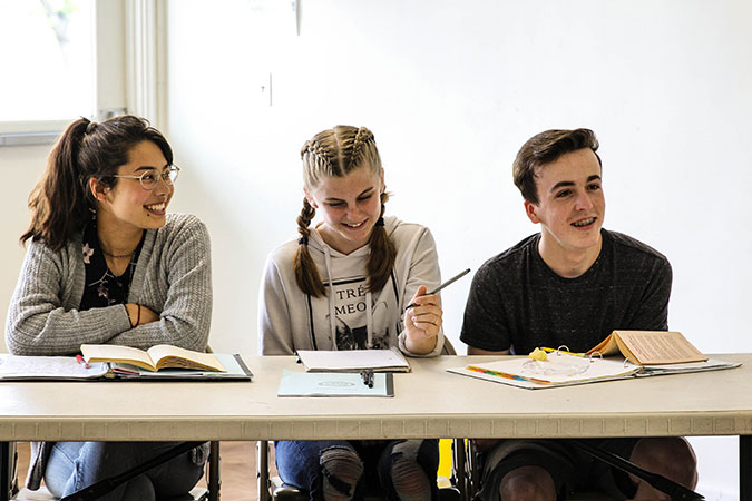 Students sit a table together in class