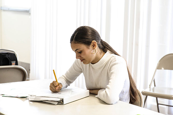 A girl in a white sweater studies and takes notes in a notebook