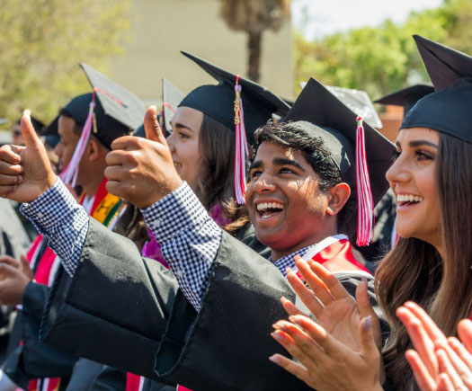 Graduates smiling and holding thumbs up