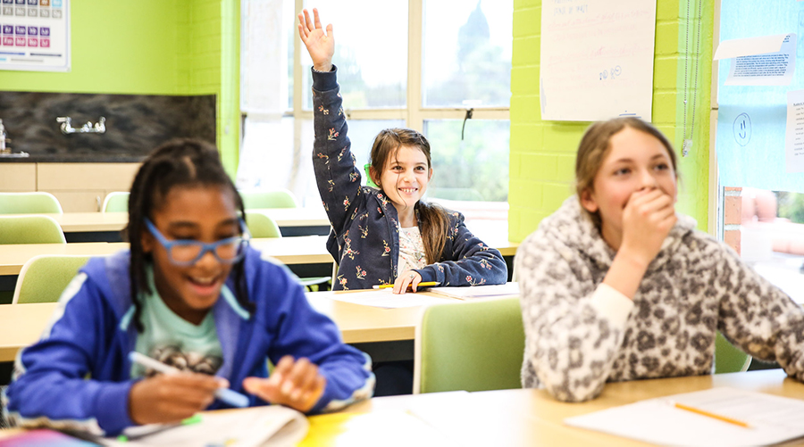 photo of three elementary students in class