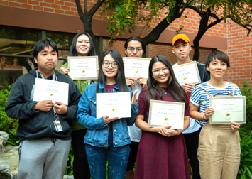 ELP students holding certificates of achievement