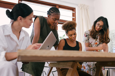 Four females of diverse ethnicity looking at a computer