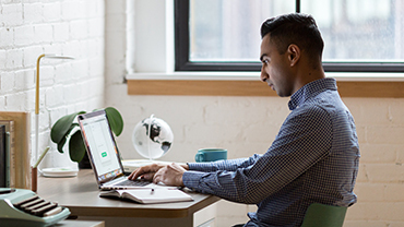 Male student sitting at desk and looking at computer