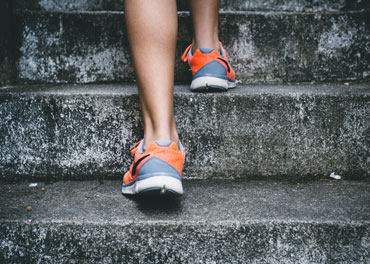 Image of person running up the stairs with orange shoes