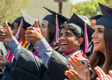 Happy Biola graduates reaching out with thumbs up signs