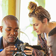 Biola journalism student with a Haitian student with camera.