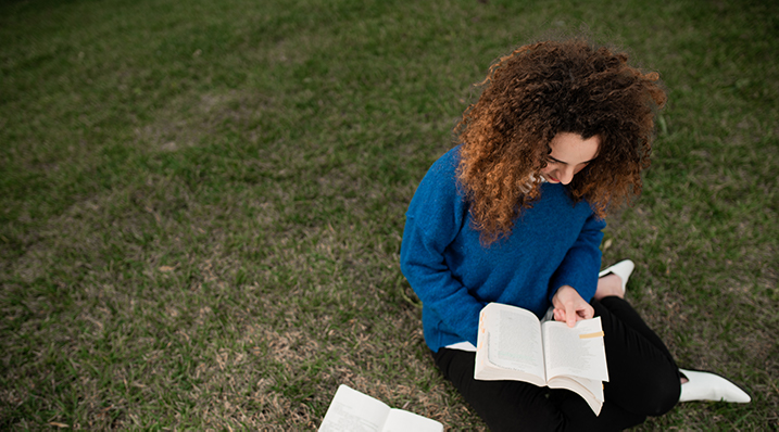 student reading a book on the lawn