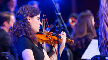 A female student playing the violin during a concert.