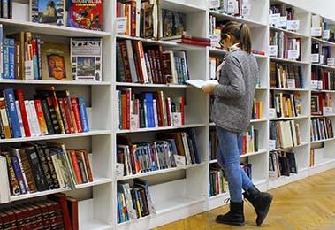 a student exploring books on shelf