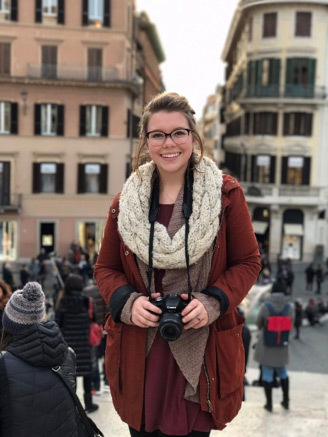 chloe standing in Rome street with camera