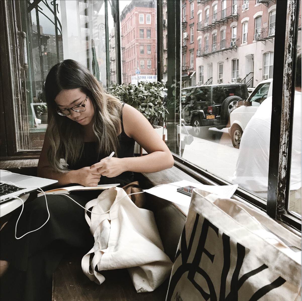 Leah Lu writing at a coffee shop in New York