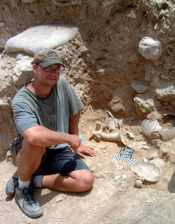 Kenneth Way sitting near  vessels which contain organic remains from ninth-century BC Philistia