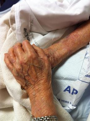 Dr. Jung's mother holding Sam Joe's hands in his final moments