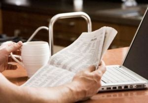 Person reading the newspaper and drinking coffee