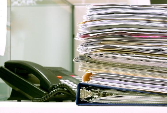 Large stack of papers and office telephone