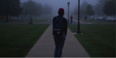 Student standing outside on a dark night