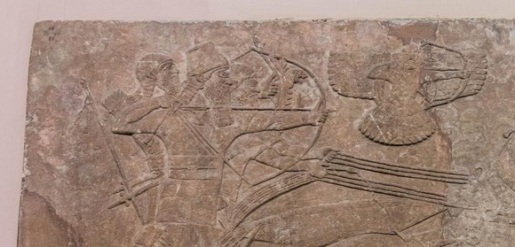 Relief of Ashurnasirpal II shooting the enemy with a bow and divine warrior Ashur